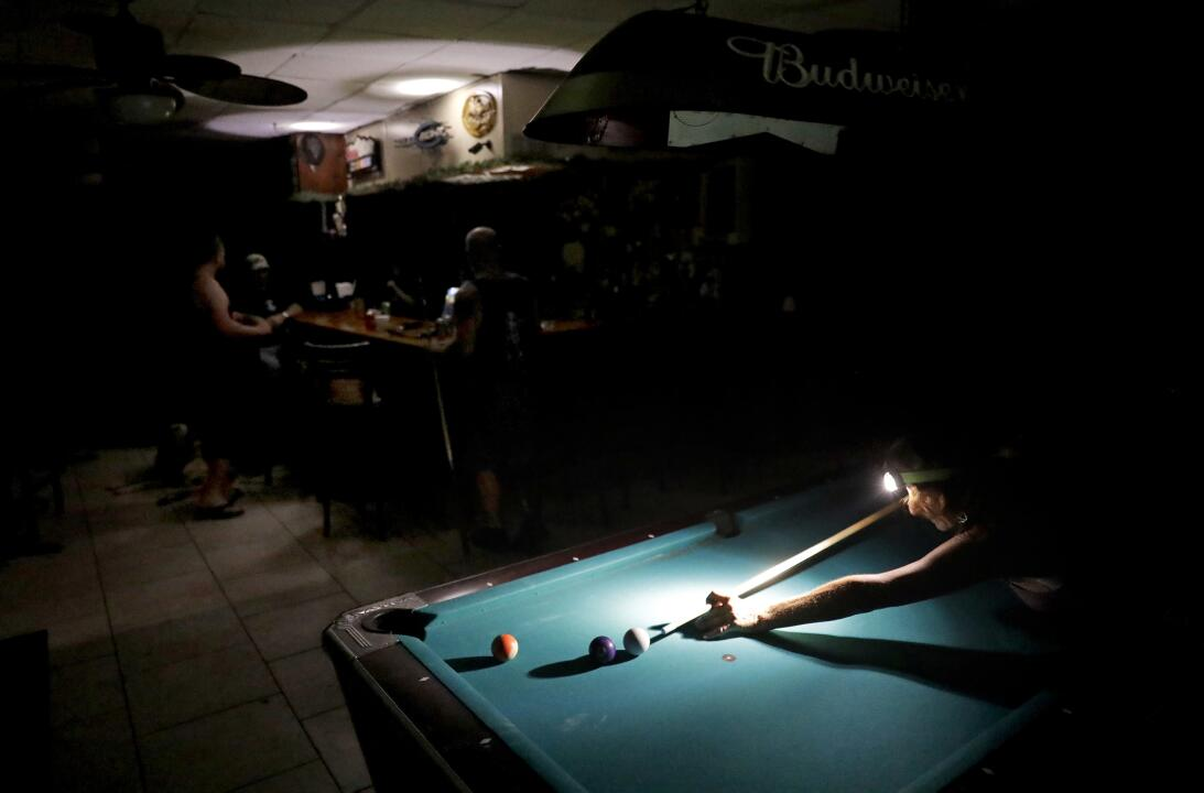 Lisa Borruso plays pool using a headlamp as the power remains out follow...