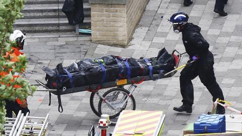 Trabajadores de Emergencias transportan un cadáver de la Torre Gr...