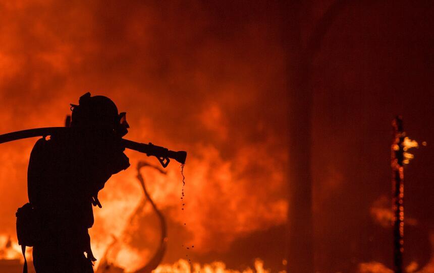 Un bombero saca una manguera frente a una casa en llamas en la región vi...