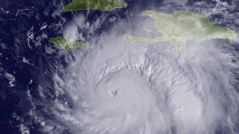A satellite image of Hurricane Matthew sitting over the central Caribbea...