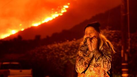 Una residente de la ciudad La Conchita llora frente al fuego del incendi...