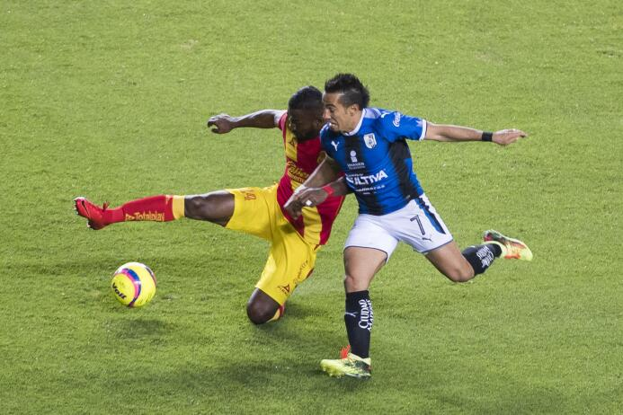 El delantero de Querétaro, Camilo Da Silva, intenta desbordar por las ba...
