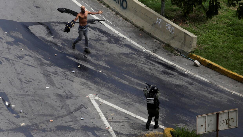 Un manifestante se acerca a un guardia nacional que lo apunta con una es...