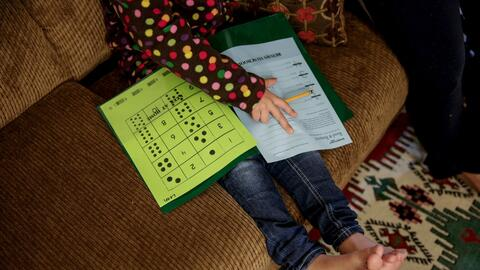 Five-year-old Syrian refugee Leen works on her homework in Sacramento in...