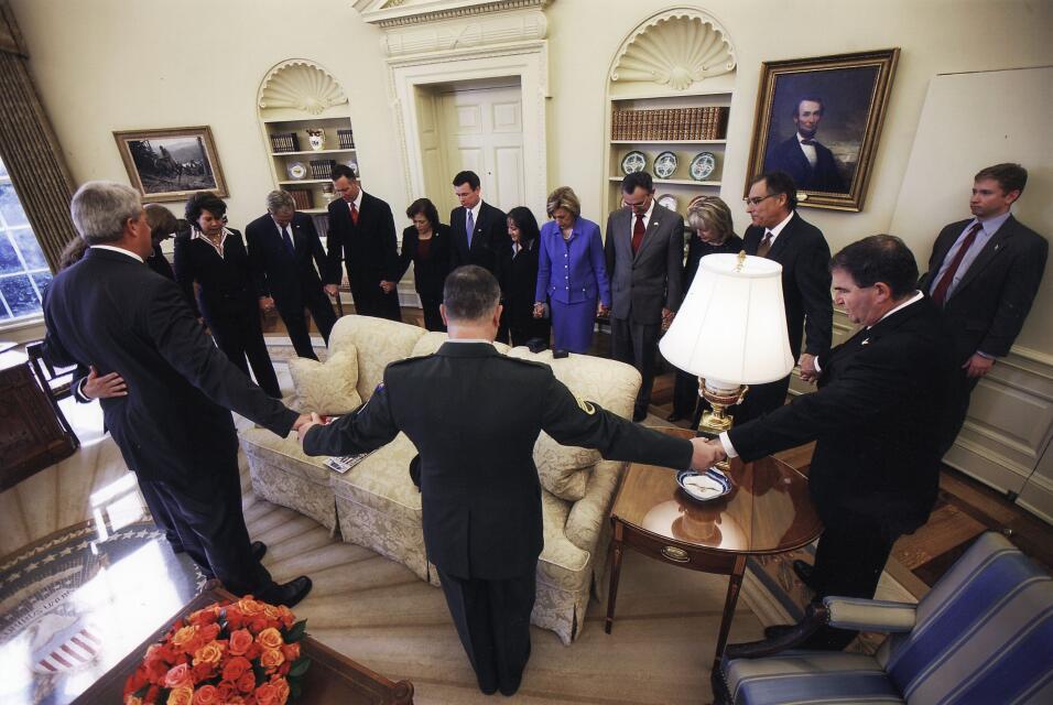 El presidente George W. Bush y algunos invitados hacen un circulo y oran...
