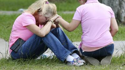 Dos mujeres rezan afuera del lugar donde los padres se reúnen con...