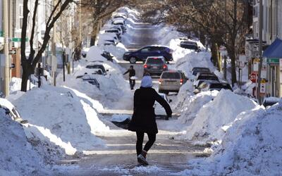 Estos vecinos de Boston palean nieve acumulada en la vía principal.