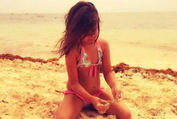 Su pequeña Michaella jugueteando con la arena de las bellas playas mexic...