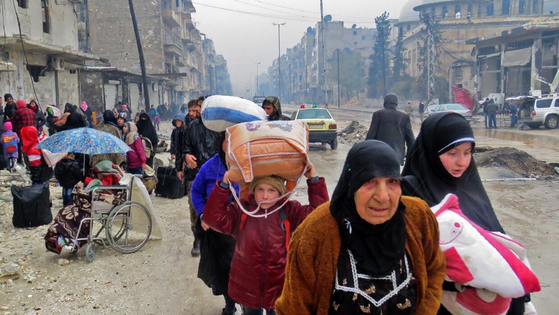 Residentes de Alepo, en Siria, huyen de la ciudad el 13 de diciembre de...