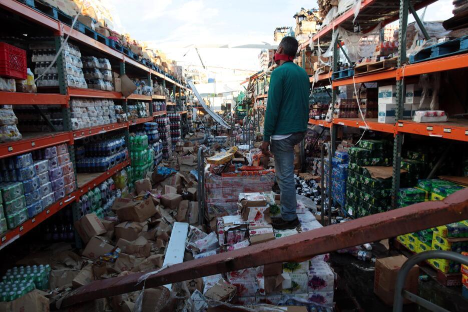 Un hombre camina dentro de un supermercado devastado por el huracán Marí...
