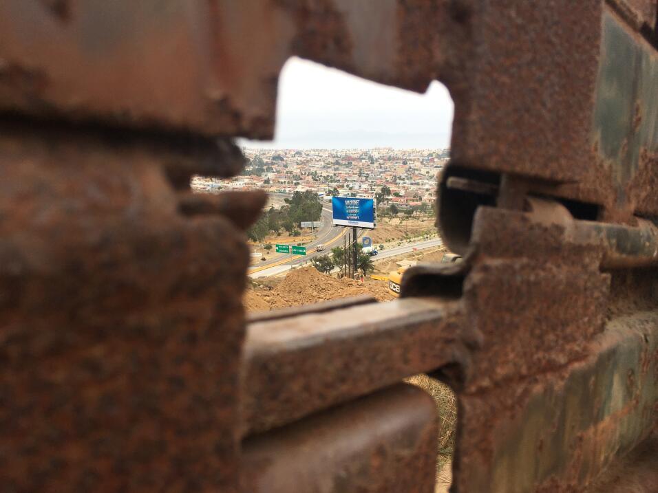 Un cartel publicitario en Tijuana se observa a través del viejo c...