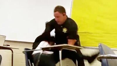 Forcejeo entre el policía y la alumna