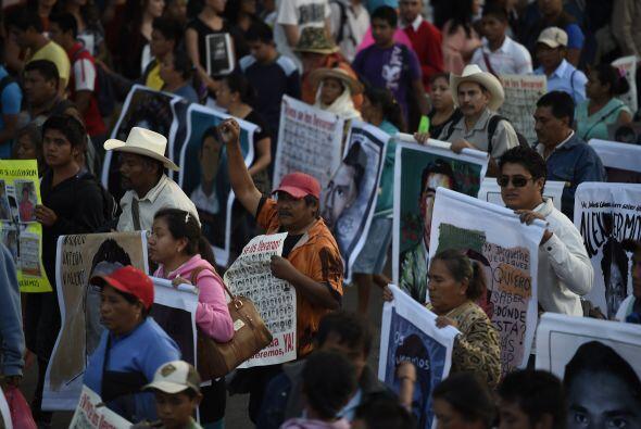 Los padres de los estudiantes asistieron a la marcha portando las fotogr...