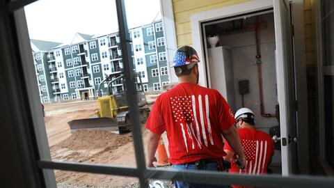 Un grupo de electricistas termina los detalles en un condominio para alq...