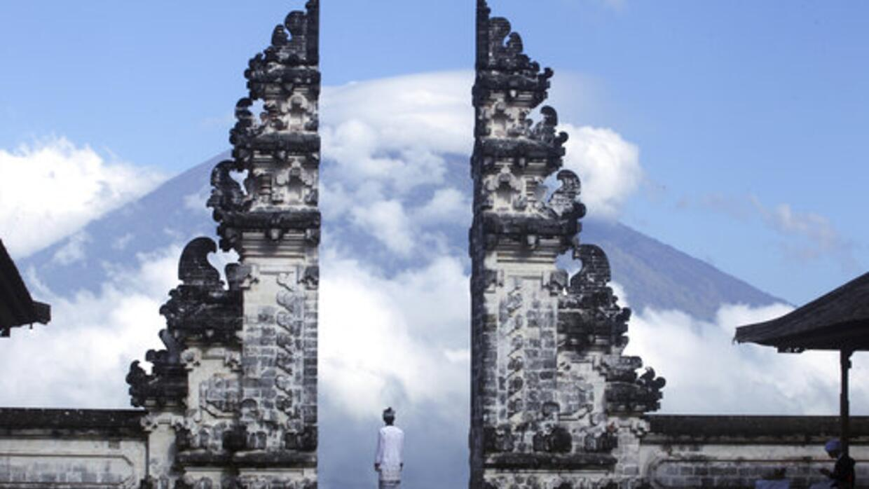 Un hombre balinés observa el volcán Agung desde un templo...