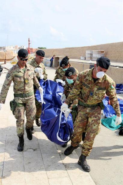 Varios hombres trasladan el cuerpo de uno de los 94 inmigrantes muertos...