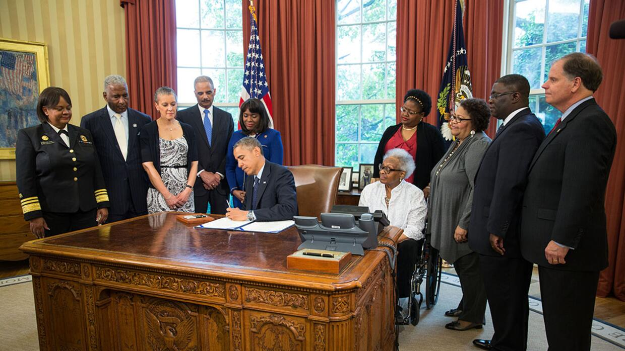 President Barack Obama signs a bill in the Oval Office designating the C...
