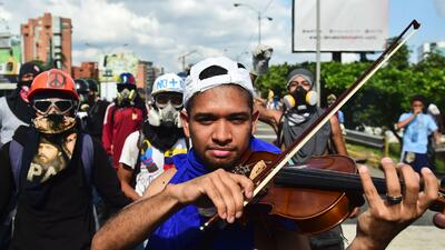 In photos: the killing of a violinist sends Venezuelan musicians onto the streets to protest