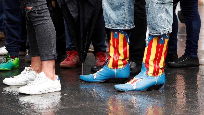 Una votante acude al referendum con unas botas con la bandera estelada,...