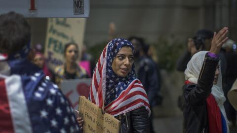 Una mujer cubierta con la bandera de EEUU como el típico velo de...