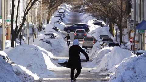 Mollie Lane, al centro, carga una pala llena de nieve hacia una pila mie...