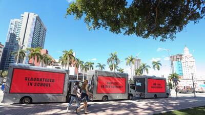 Tres vallas publicitarias instaladas en camiones estacionados frente a l...