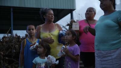 Mujeres y niños afectados por el huracán reciben comida y agua de volunt...
