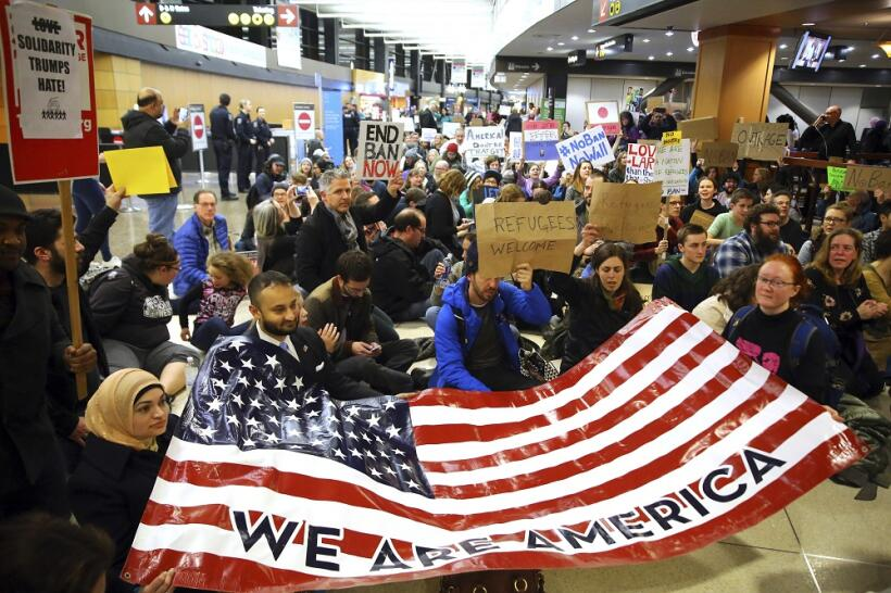 Manifestantes en el Seattle-Tacoma International Airport con una bandera...