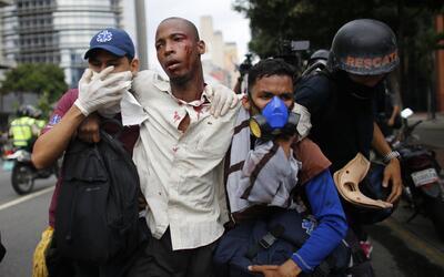 Paramédicos asistiendo a un hombre herido en los enfrentamientos...