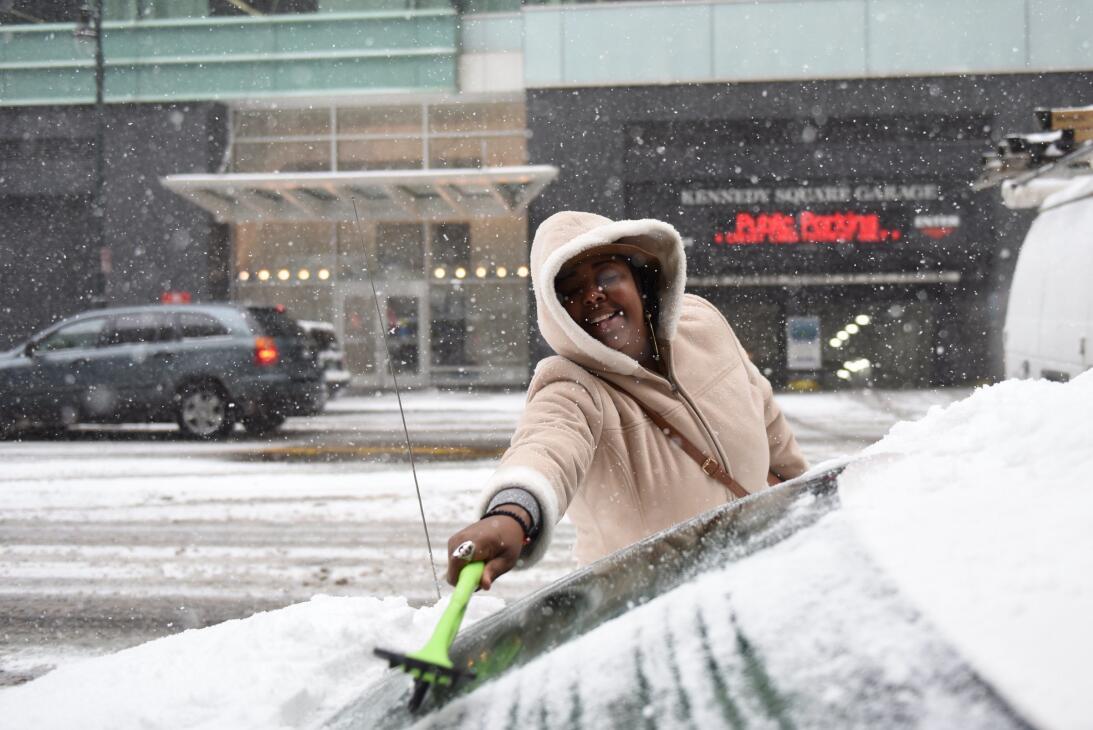 Esta mujer limpia el parabrisas de su automóvil cubierto por una capa de...