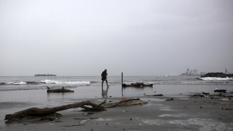 Un hombre camina por la playa antes de la llegada del huracán Fra...