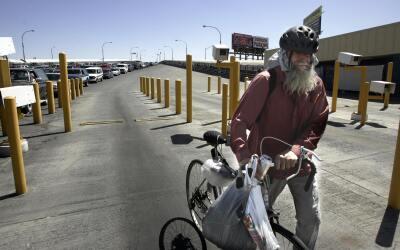 Un hombre cruzando la frontera de El Paso y Ciudad Juárez en su b...