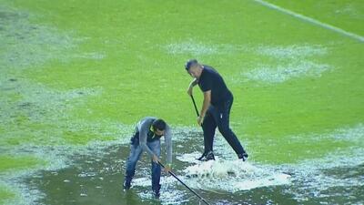 Ayudantes tratan de sacar con celeridad el agua de la cancha de León