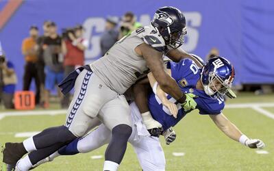 Sheldon Richardson, de los Seahawks de Seattle, a la izquierda, derriba...