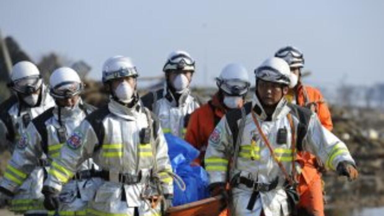 Personal de rescate llevan una de las tantas víctimas en la zona costera...