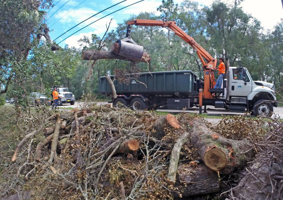 Workers from Seminole County Roads-Stormwater remove yard waste from Hur...
