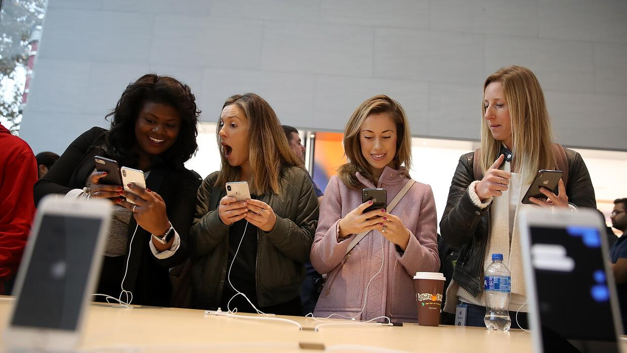 Shoppers examine the new iPhone X at an Apple store in Palo Alto, Califo...