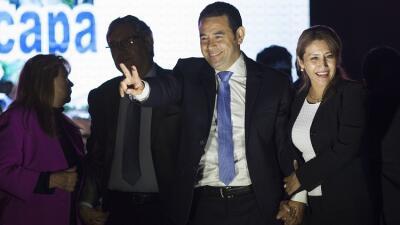 Morales (centro) realiza el símbolo de la victoria junto a su esposa Hilda.