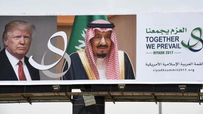 Una imagen de Trump junto al rey Salman de Arabia Saudita en una valla p...