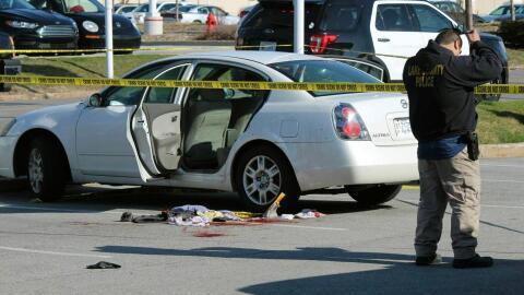 Un policía junto al auto donde la mujer recibió el disparo...