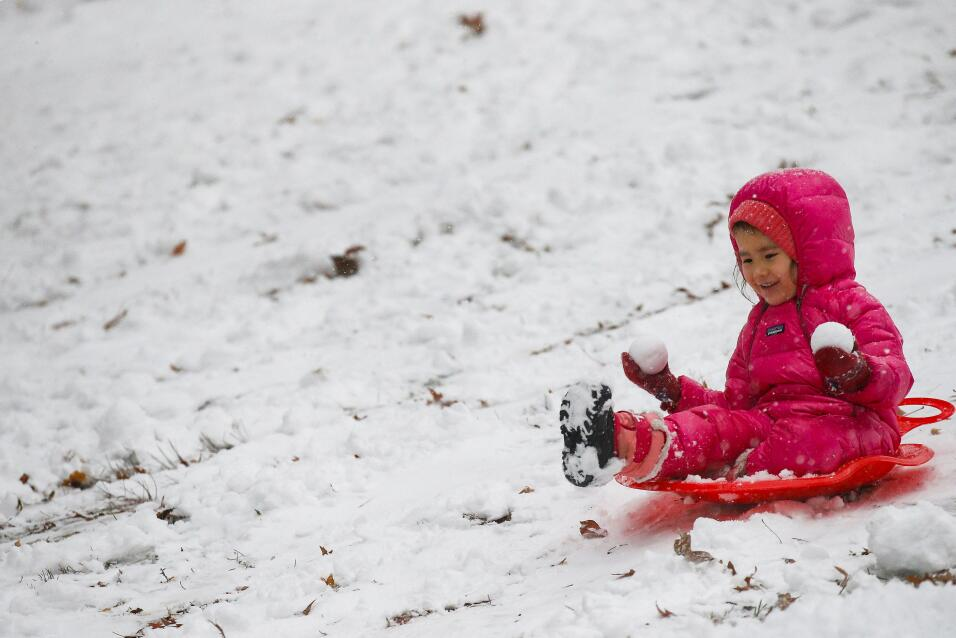 A child rides in a sled in Central Park during a pre-winter storm in New...
