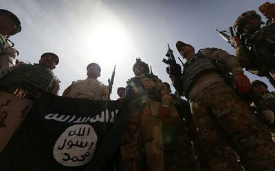 Soldados iraquíes sostienen una bandera de ISIS tras tomar el con...