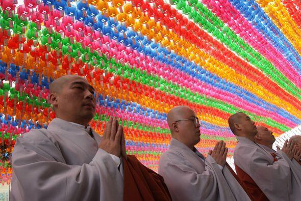 Monjes budistas rezan mientras los niños se convierten en monjes.