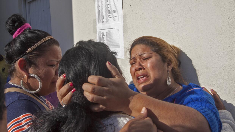 Familiares de las víctimas reaccionan al leer el listado de nombres.