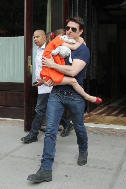 US actor Tom Cruise leaves his hotel carrying daughter Suri for her gymn...