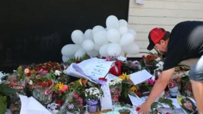 Decenas de personas dejaron ofrendas florales y una gran pancarta con un...