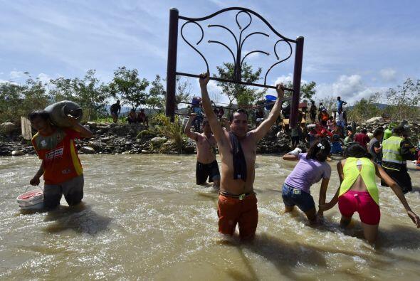 Colombianos deportados por Venezuela cargan con sus pertenencias.