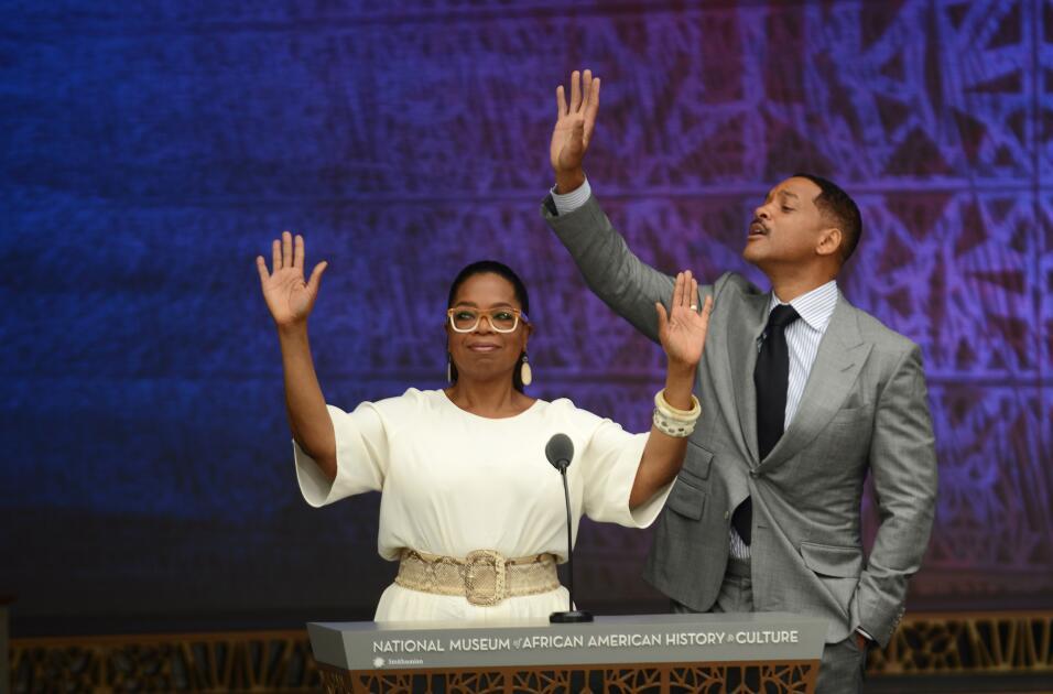 Oprah Winfrey y Will Smith saludar a la multitud antes de citar textos d...