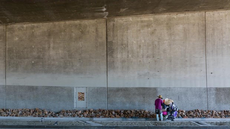 Una mujer sin hogar detiene su carrito de compras enfrente del recién in...