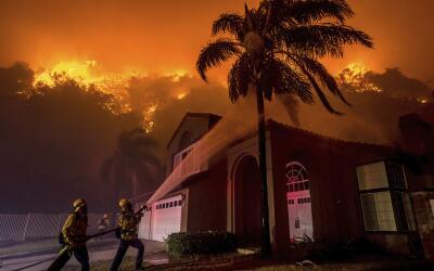 Dos bomberos rocían agua sobre una vivienda en Corona durante el...